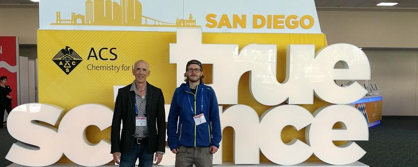 Dr. Karl N. Kirschner and PhD Student Robin Strickstrock in front of the ACS conference sign