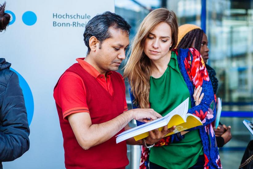 Two international students of the MBA Programm are standing together in front of the main Campus Building Entrance and are looking together into a book.